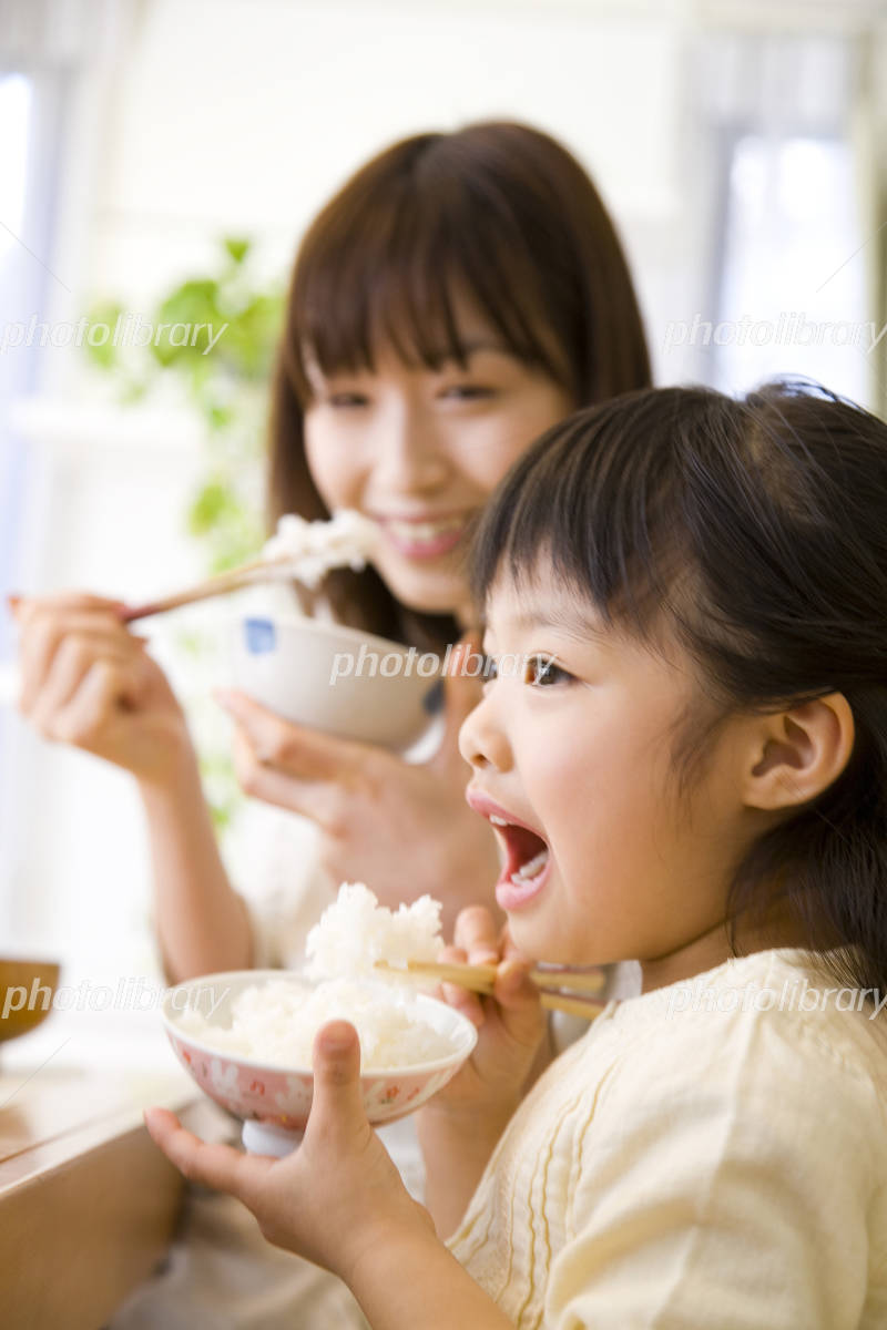 Mother and daughter eating rice Photo