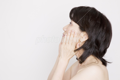 Woman to care about the skin along with a hand on his cheek Photo