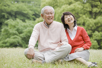 Elderly couple sitting a conversation on the grass in the park Stock photo [2390820] 2