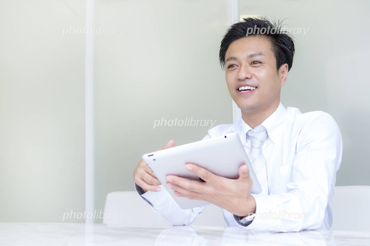 Businessman speaking with a tablet Photo