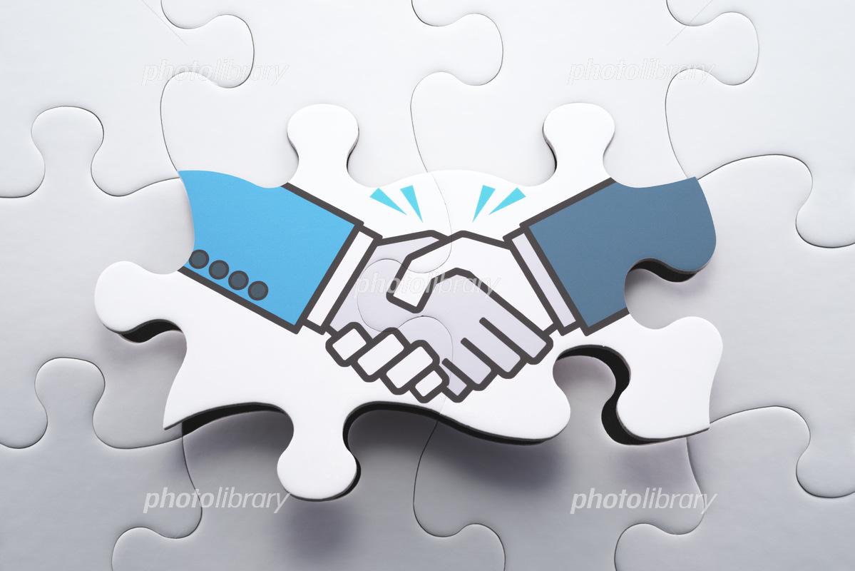 合意形成や戦略的パートナーシップのイメージ 握手するイラストが描かれたジグソーパズルの写真