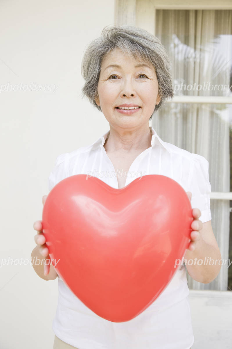 Senior woman with a heart-shaped balloon Photo