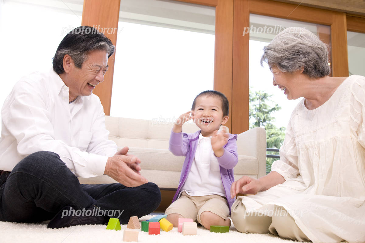 Grandfather and grandmother playing with grandchildren and building blocks Photo