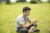 View Video listen to the smartphone music generic male teens twenties outdoor park green grass Stock photo [4594988] smartphone