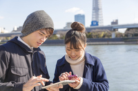 Couple male and female smartphone and tablet search examine outside sunny Sumida River Stock photo [4659110] smartphone