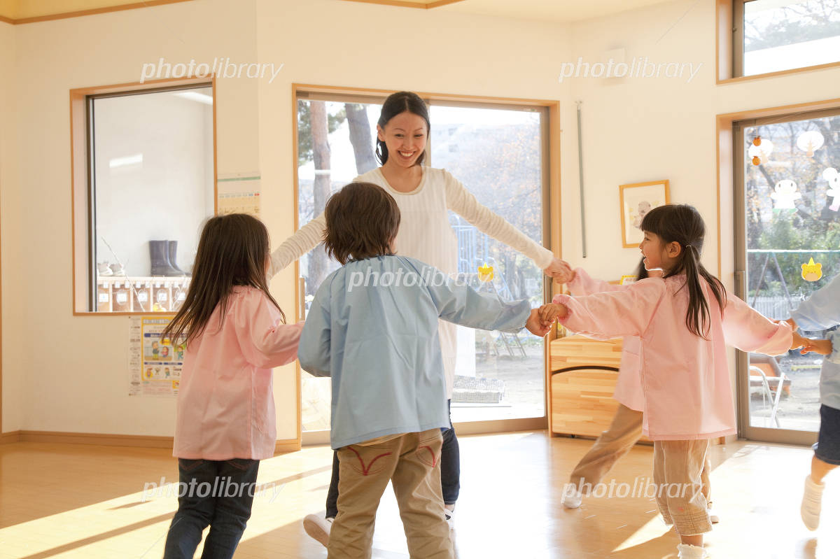 Kindergarten teachers and kindergarten children dancing in a circle Photo