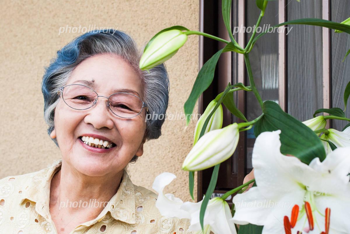 Senior women rejoice in flowering of lily Photo