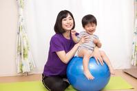 写真 The child riding the balance ball and the mother supporting it(5117043)
