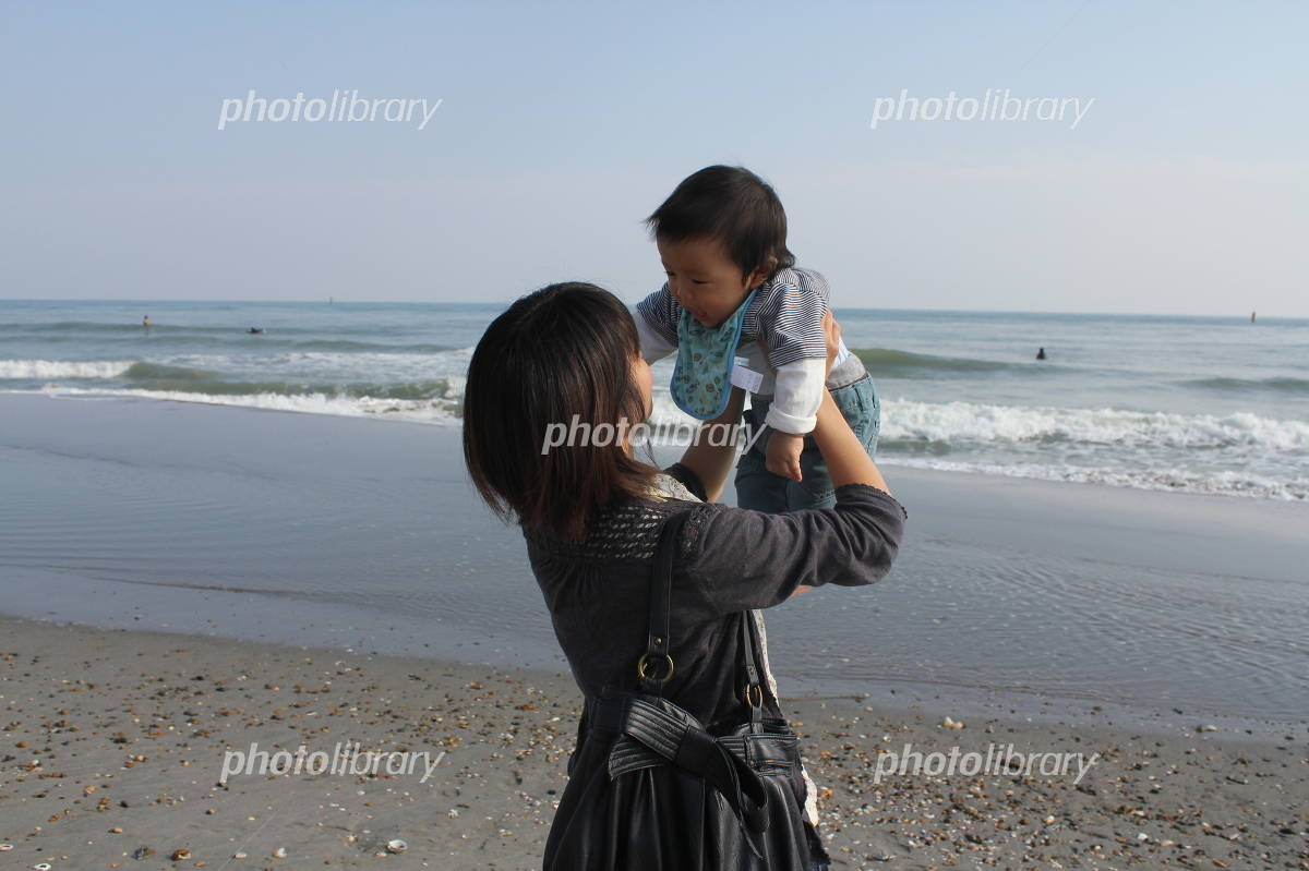 Parent and child playing on the beach Photo
