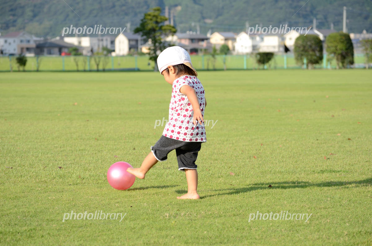 Children kicking a ball barefoot Photo