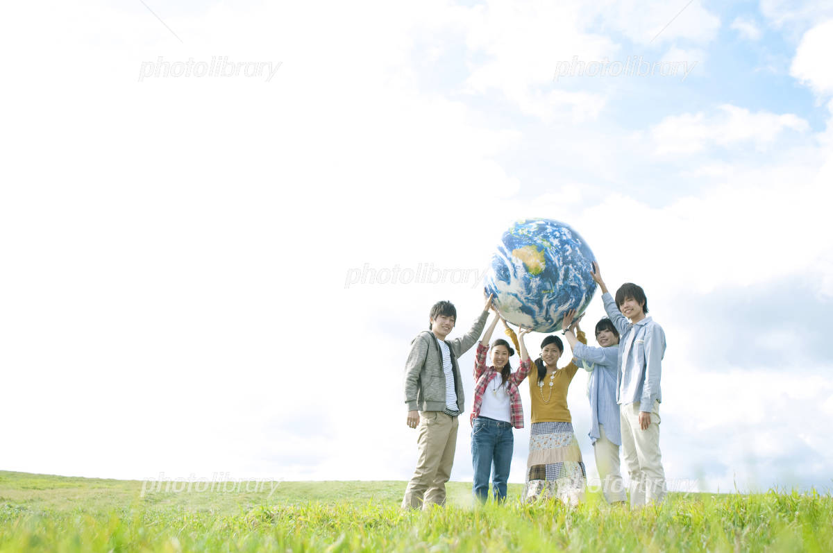 Young people with the Earth's ball in grassland Photo
