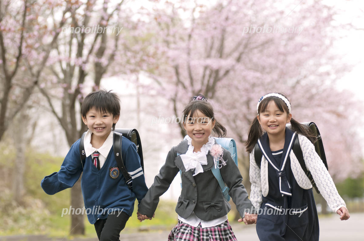 Elementary school students running the cherry tree-lined street Photo