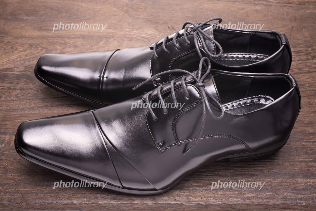 木のテーブルの上の横向きの黒い革靴 写真素材 [ 4956761
