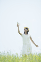 A woman flying a paper airplane in the meadow Stock photo [5066684] Prairie