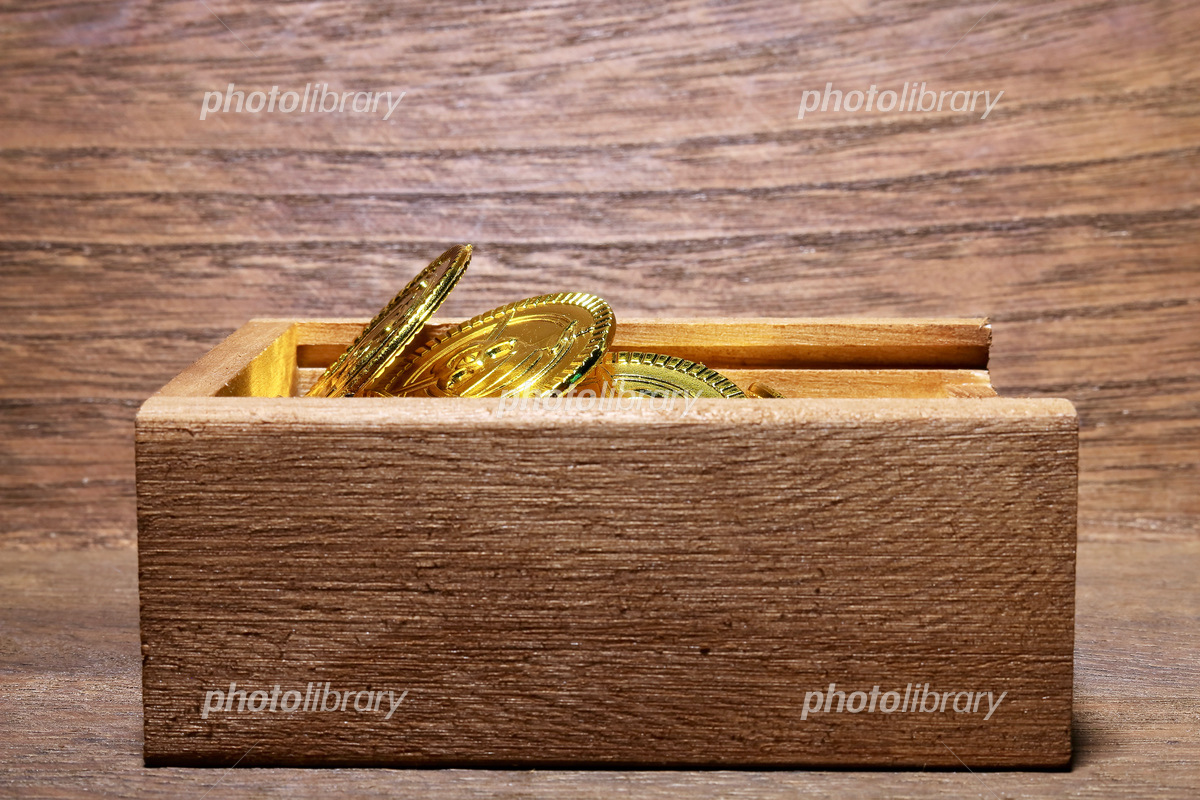 Toy gold coin and wooden box Photo