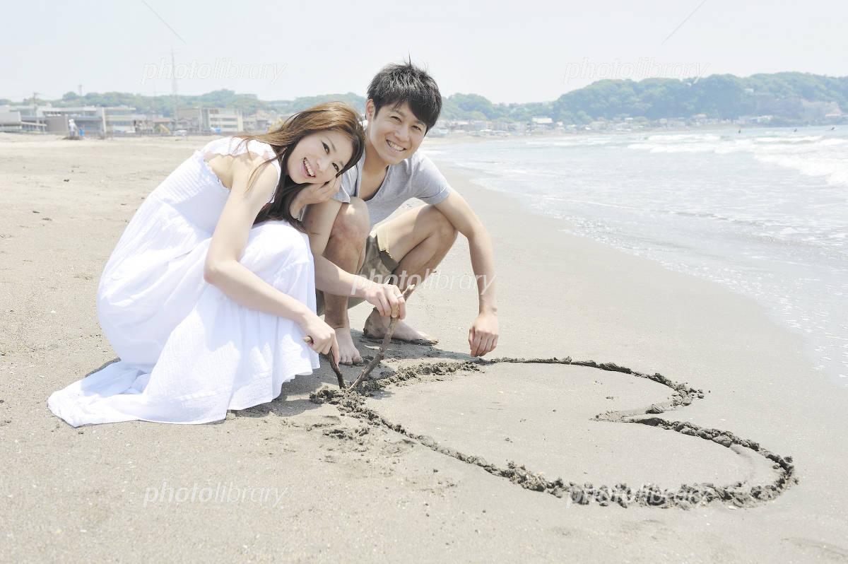 Couple to write a heart on the beach Photo