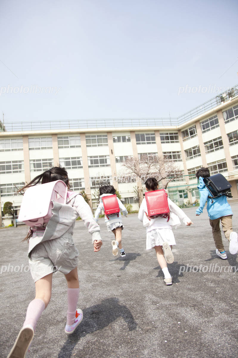 Rear View of four elementary school children to school Photo
