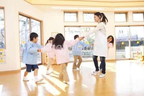Kindergarten teachers and kindergarten children dancing in a circle Photo