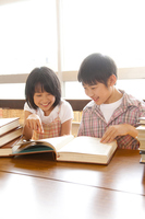 Elementary school men and women reading a book in the library Stock photo [2349043] 2