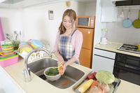 Young housewife facing the carrot of skin in the kitchen Stock photo [2692595] Female