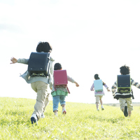 Rear View of elementary school students running the prairie Stock photo [4782882] Primary
