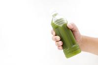 写真 Pet bottle of green juice held in hand(5588757)