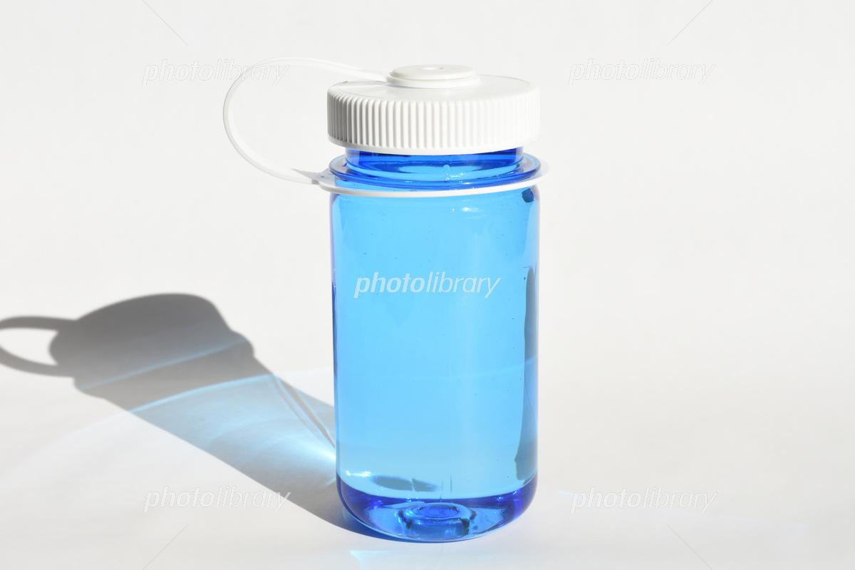 太陽光に照らされた青いボトルに入った水  写真素材