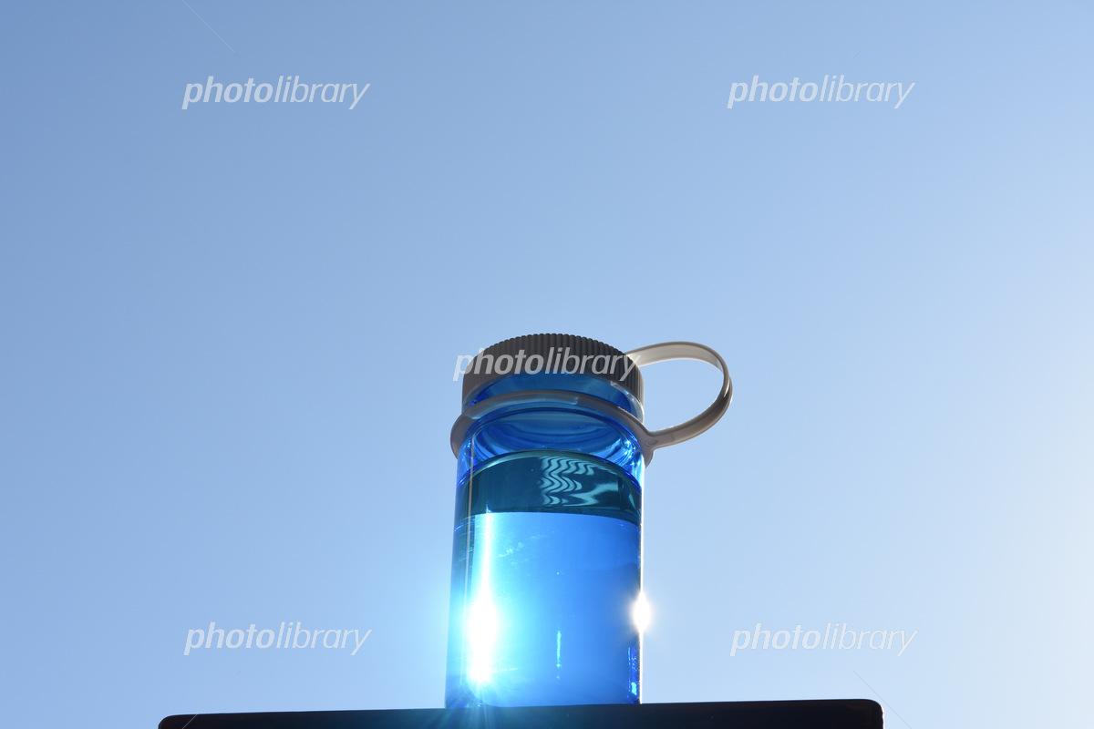 青空と青いボトルに入った水  写真素材