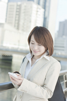 Businesswoman operating a smartphone Stock photo [1139962] Business