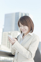 Businesswoman operating a smartphone Stock photo [1139987] Business