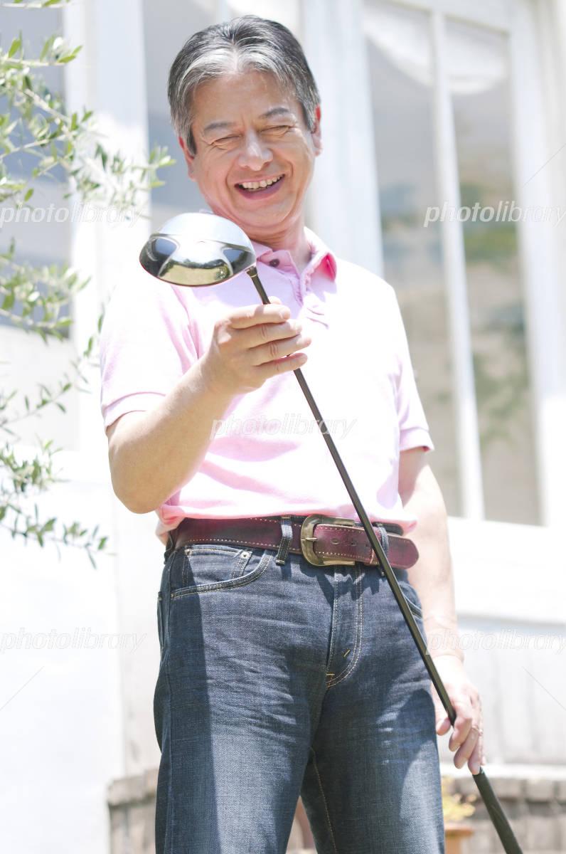 Senior man smiling with a golf club Photo