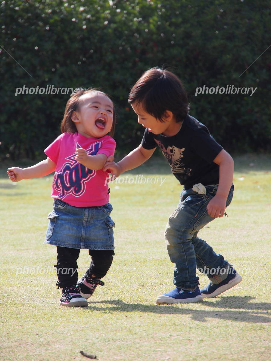 Brother and sister playing in the park Photo