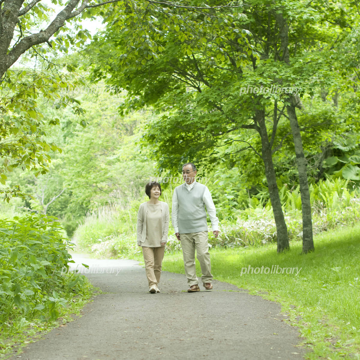 Senior couple walking in the middle of a fresh green Photo